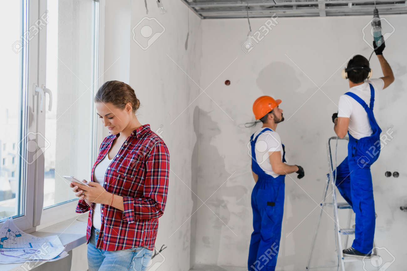 Man in overalls use drill and stepladder, woman typing on the phone - 170401029