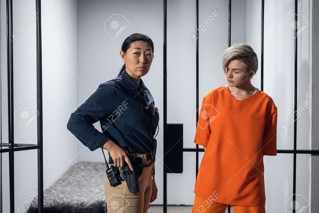 Blonde inmate in an asian womens general security prison is led out of her cell by a uniformed guard, with a holstered pistol and a walkie-talkie. - 170401005