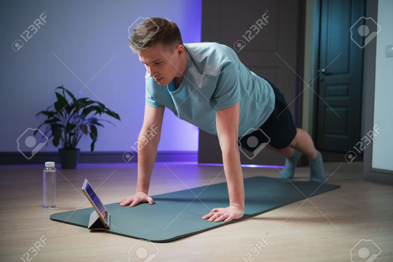 Online training of a young athlete at home on the mat, a professional coach conducts a class on the Internet - 170401011