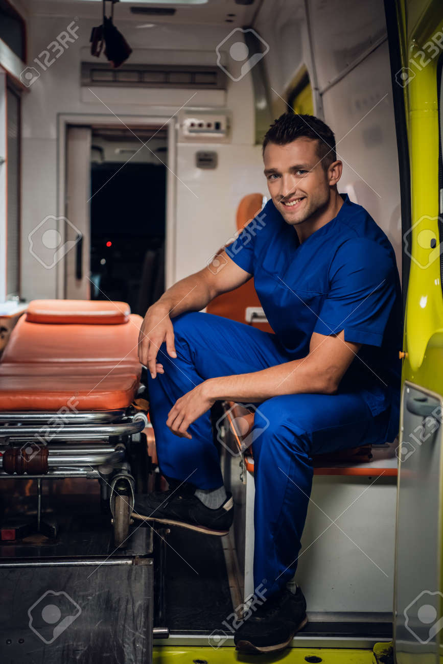 Smiling man in a medical uniform sitting in the back of an ambulance car, beside the stretcher - 170401015