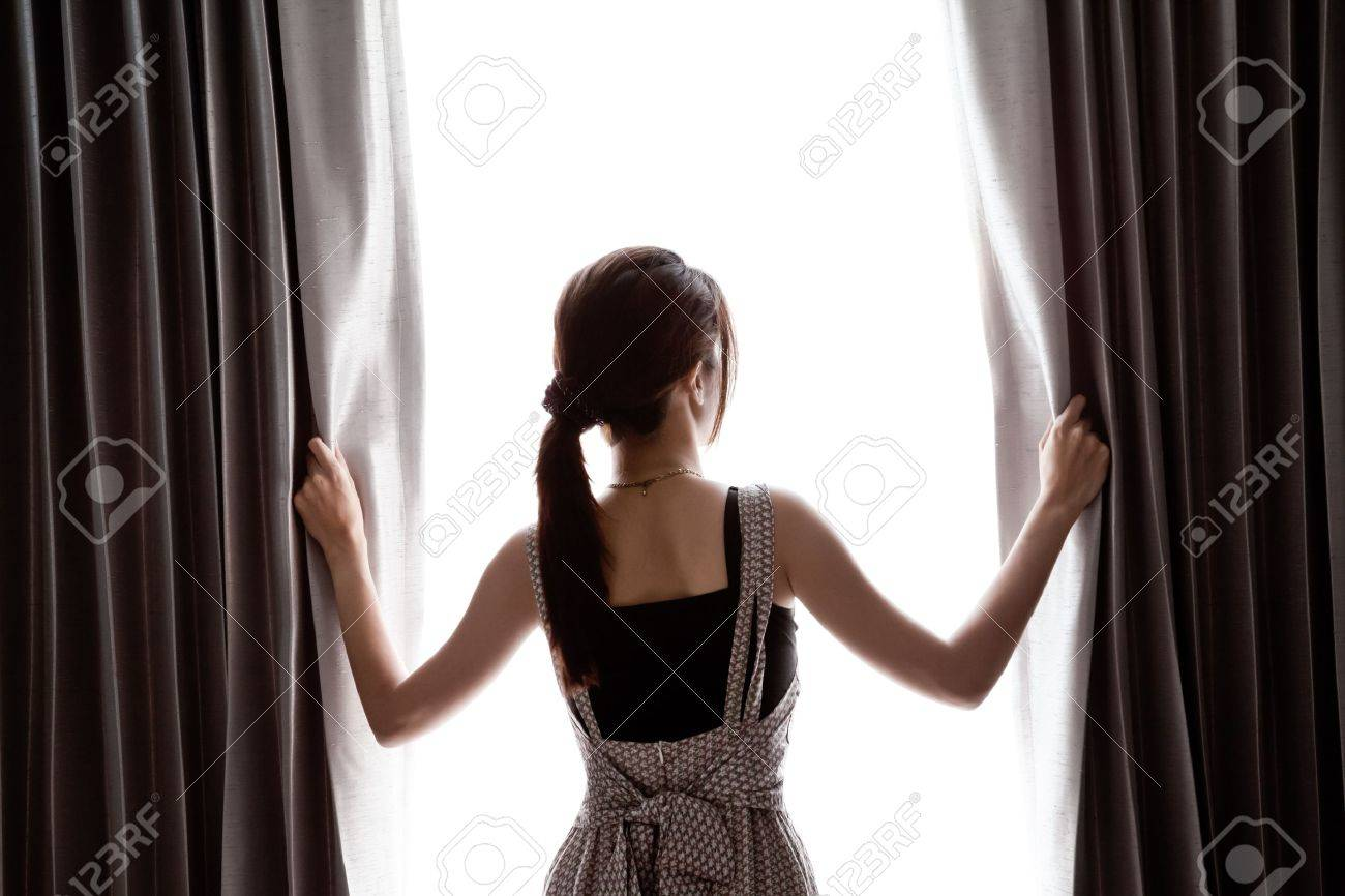 young woman opening curtains Stock Photo - 13550856