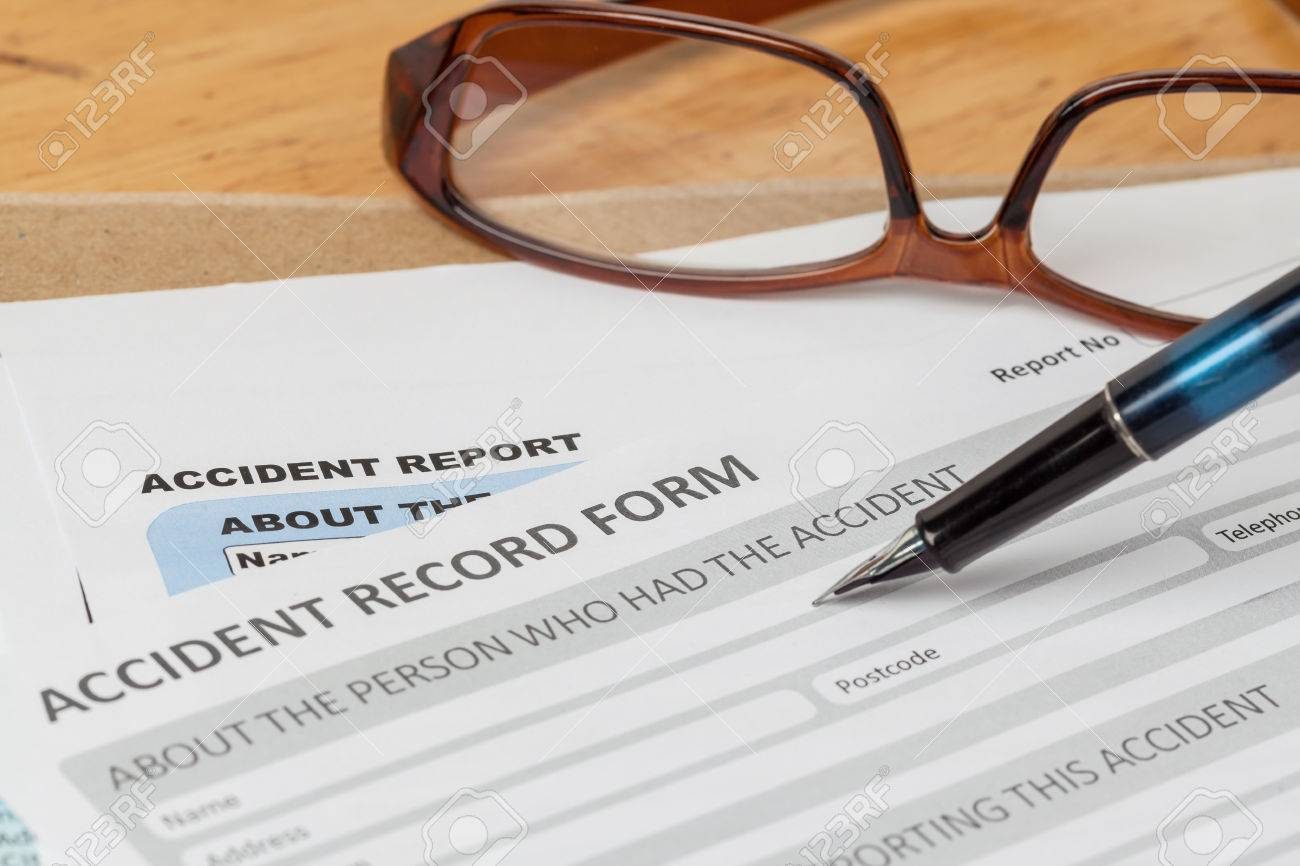 accident report application form and pen on brown envelope and accident report application form and pen on brown envelope and eyeglass business insurance and risk