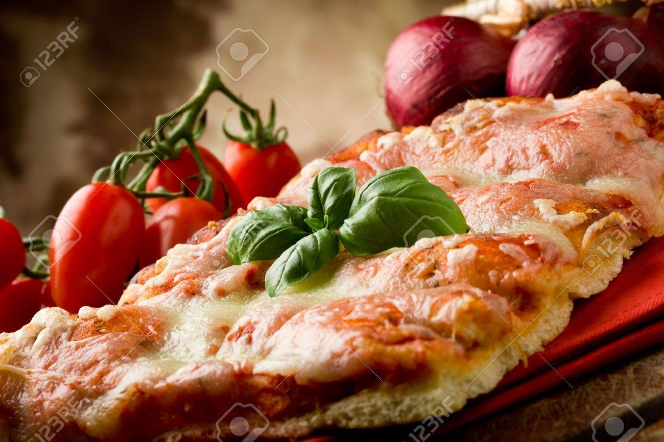 photo of delicious slice of pizza with basil leaf on it - 9456511