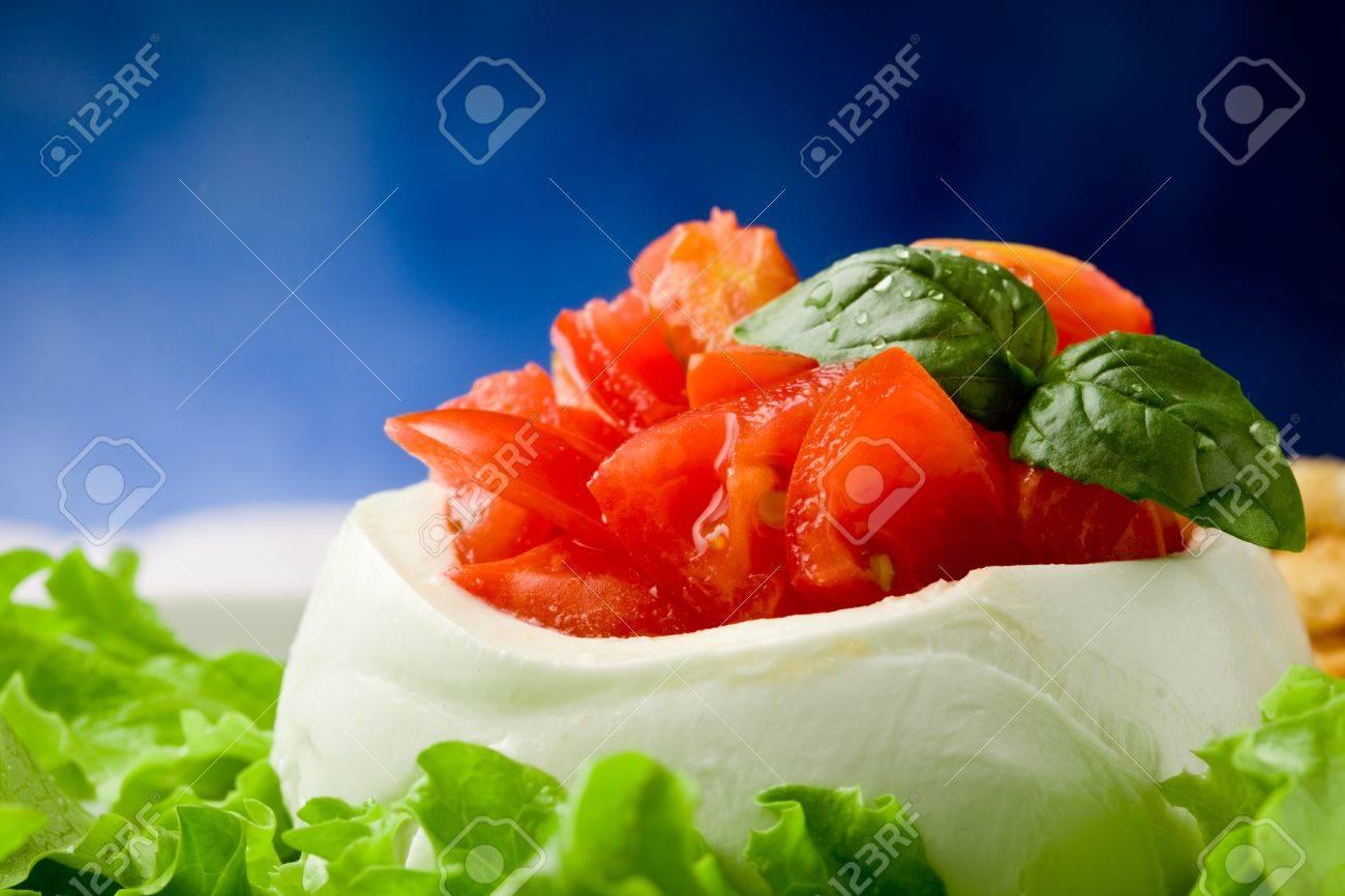 stuffed buffalo mozzarella with tomatoes and basil on lettuce over blue background Stock Photo - 9512669