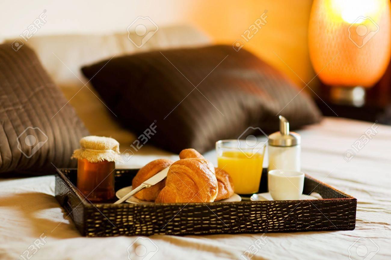 Foto van dienblad met ontbijt eten op het bed in een slaapkamer ...