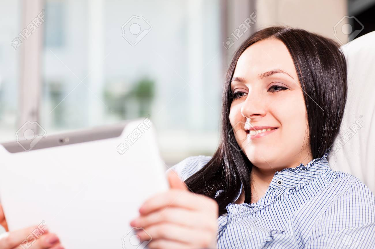 Beautiful woman at home is smiling while videocalling with a tablet Stock Photo - 13854589
