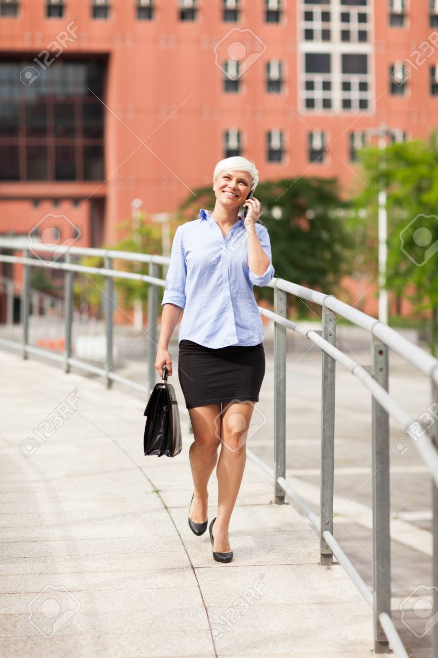 Smiling blonde businesswoman is walking while phoning and smiling Stock Photo - 22222062