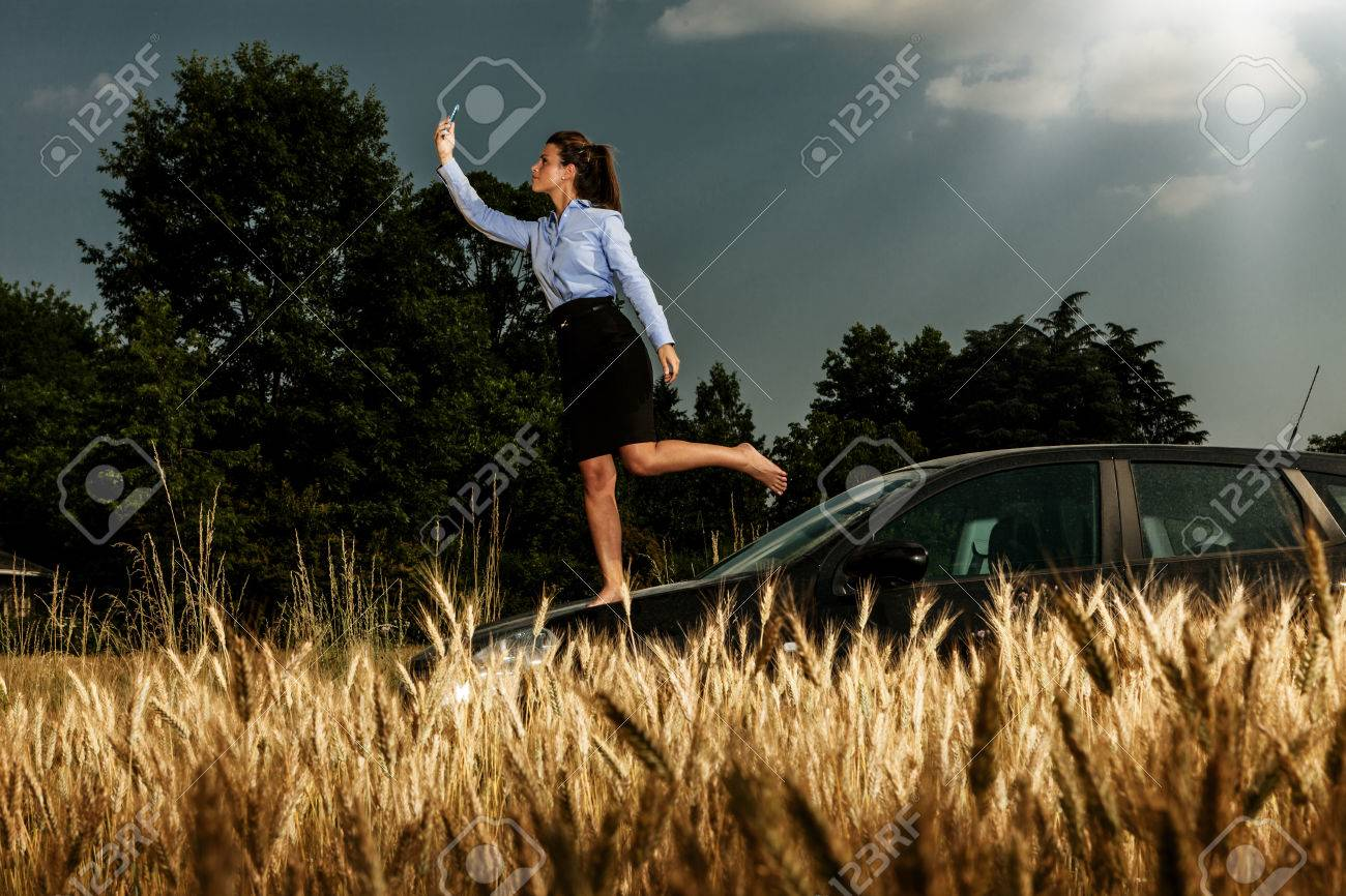 Brunette businesswoman searching for phone signal while standing on her car Stock Photo - 22222220