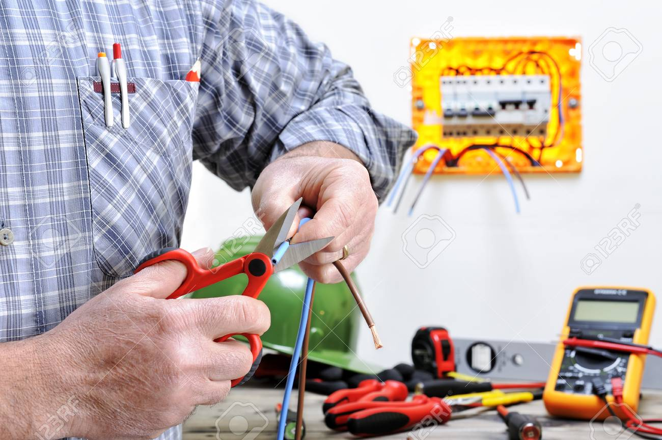 Electrician Technician At Work In A Residential Electric Wiring Installation Cuts The Cable Stock Photo