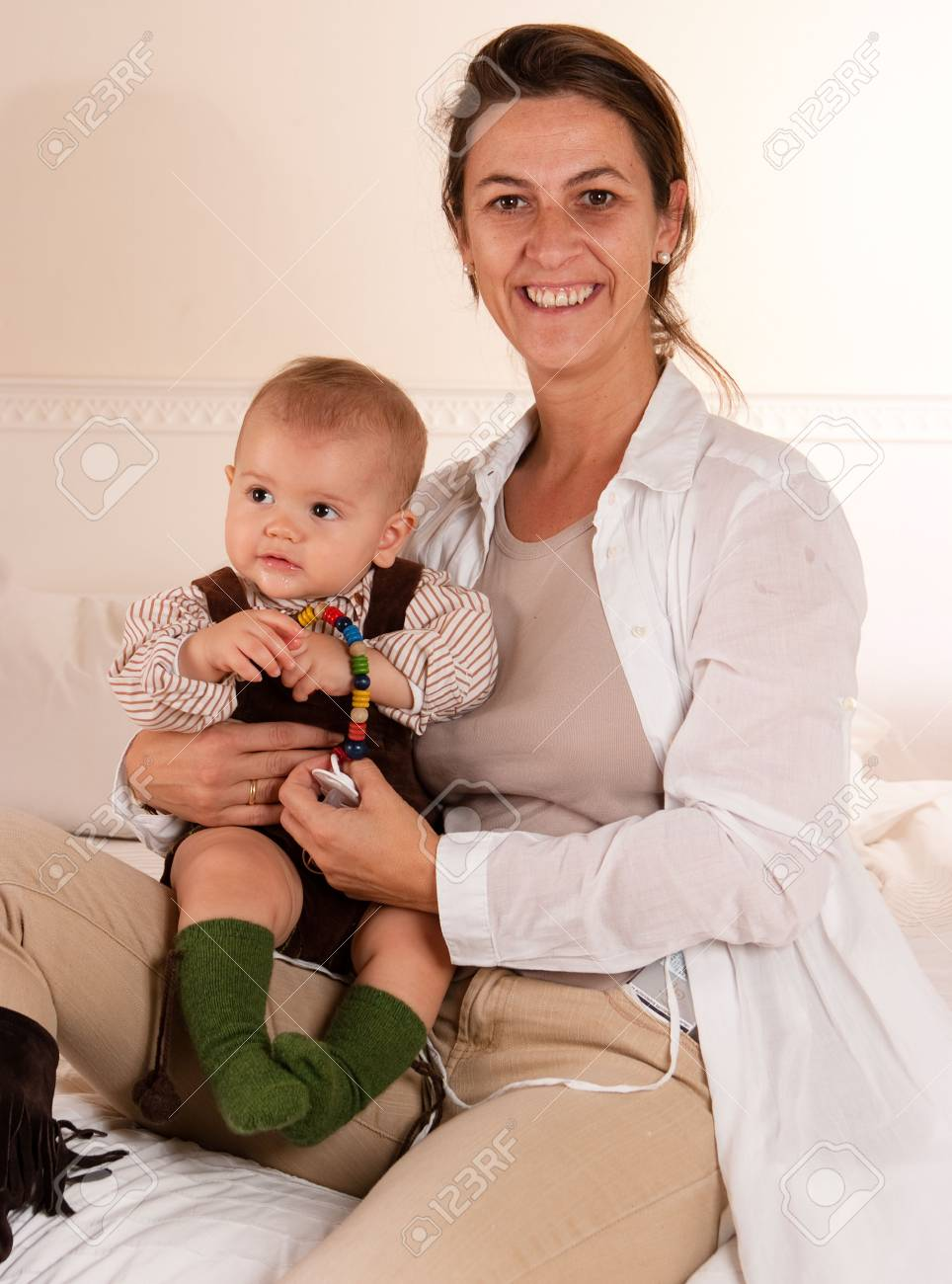 Woman sitting on a bed playing with her baby boy Stock Photo - 6332550