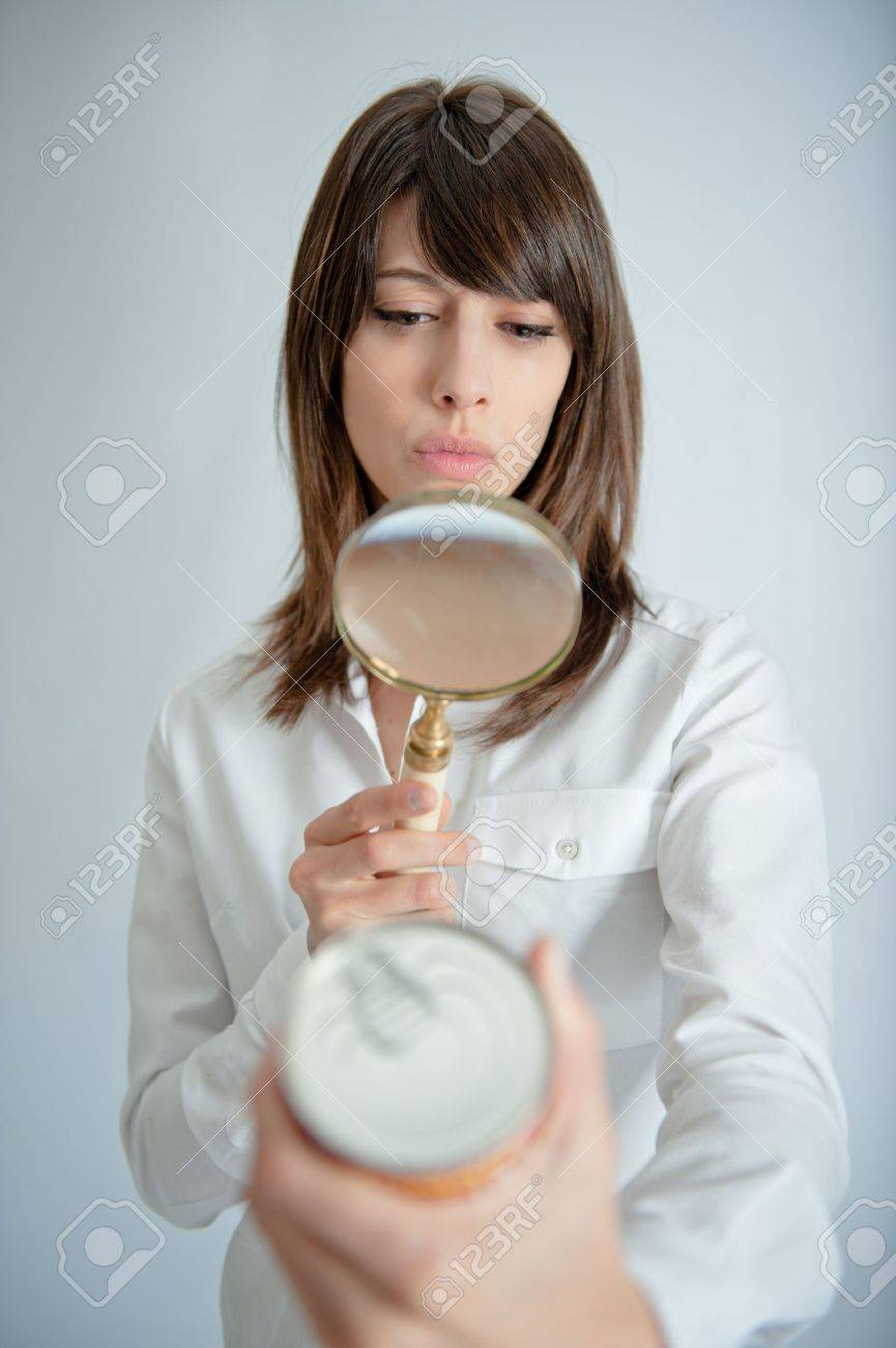 Young woman inspecting a can�s nutrition label with a magnifying glass Stock Photo - 10441910