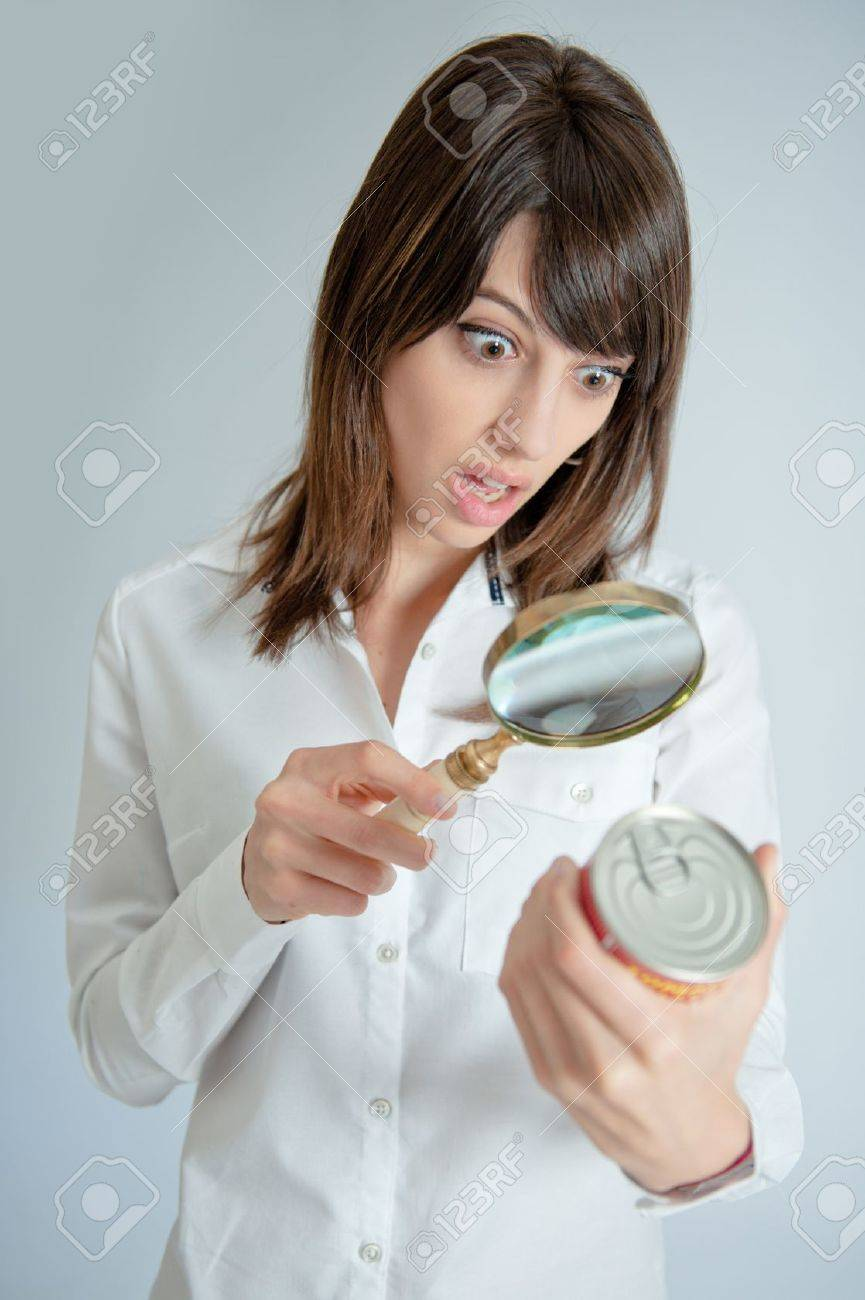 Shocked young   woman inspecting a can�s nutrition label with a magnifying glass Stock Photo - 11406879