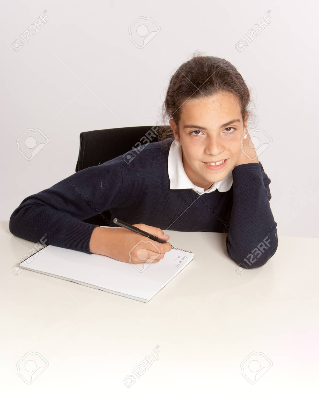 Schoolgirl writing at her desk with a happy expression Stock Photo - 11727619