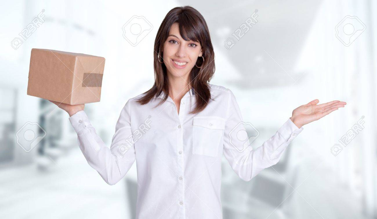 Young woman with a balance position a parcel in one hand and the other one empty against a business background Stock Photo - 13230352