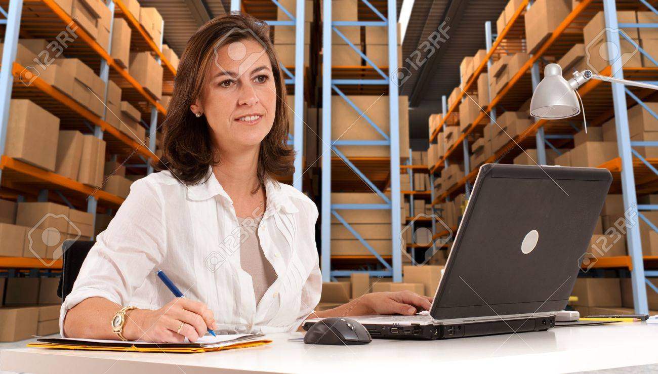 Female administrative in a desk with a distribution warehouse in the background Stock Photo - 13253519