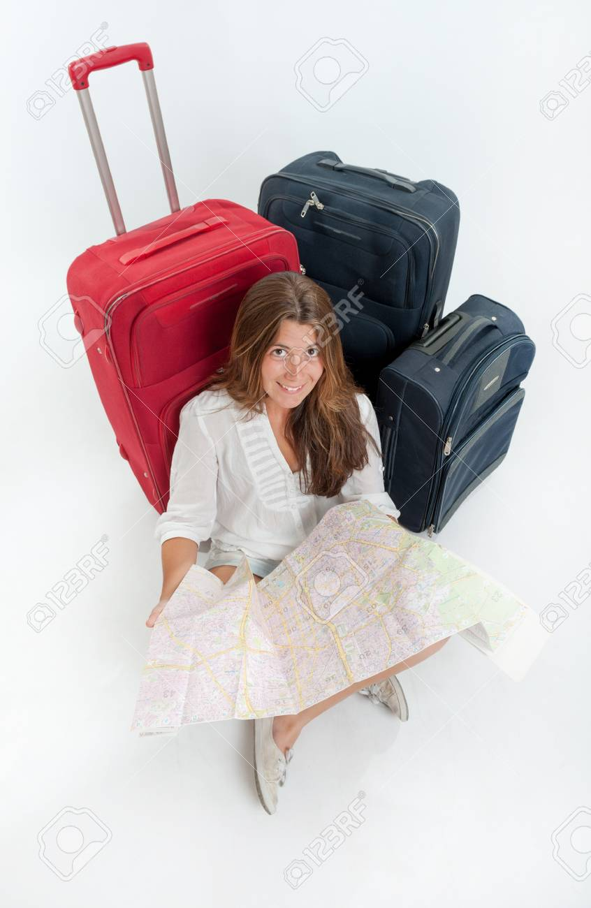 Happy young woman sitting on the floor surrounded by luggage, holding a map Stock Photo - 16657652