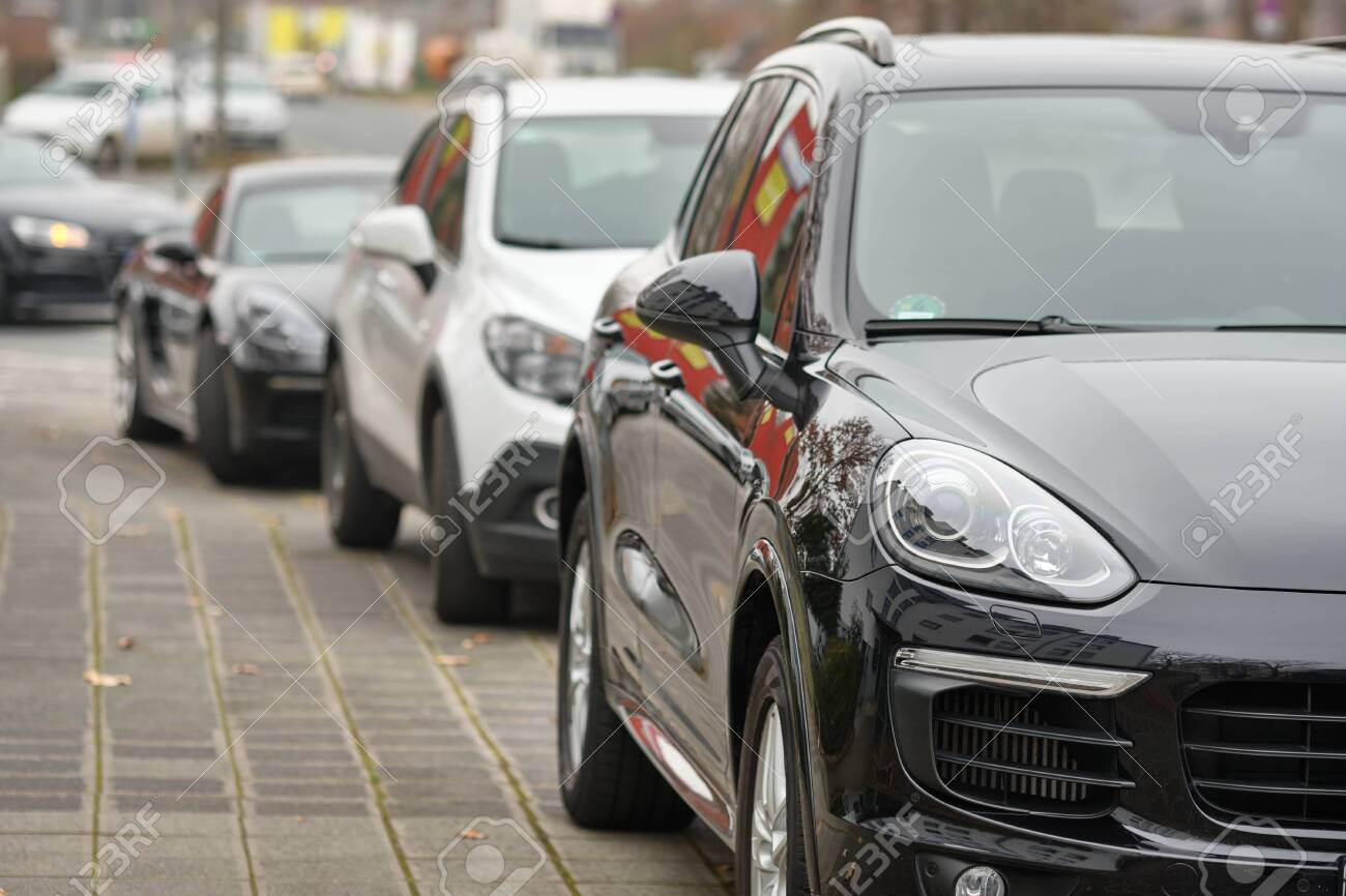 Nuremberg, Germany - December 02, 2019: Headlight of a big black Porsche SUV car parking in a row together with other cars on the pavement in the city. - 149862199