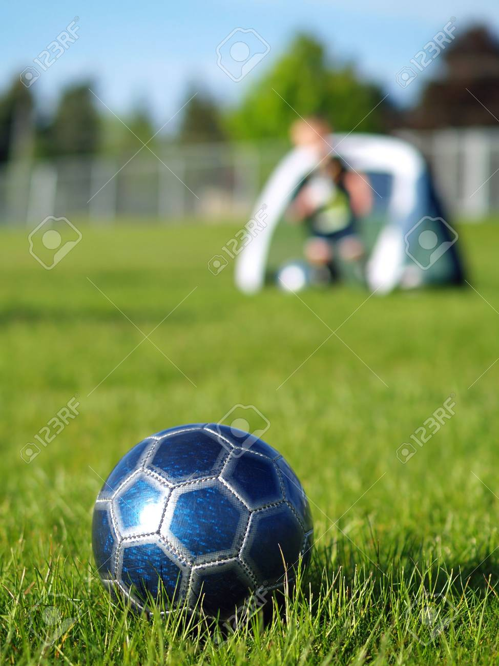 A blue soccer ball on field of green grass on a sunny day with kids in the background. Stock Photo - 5000247