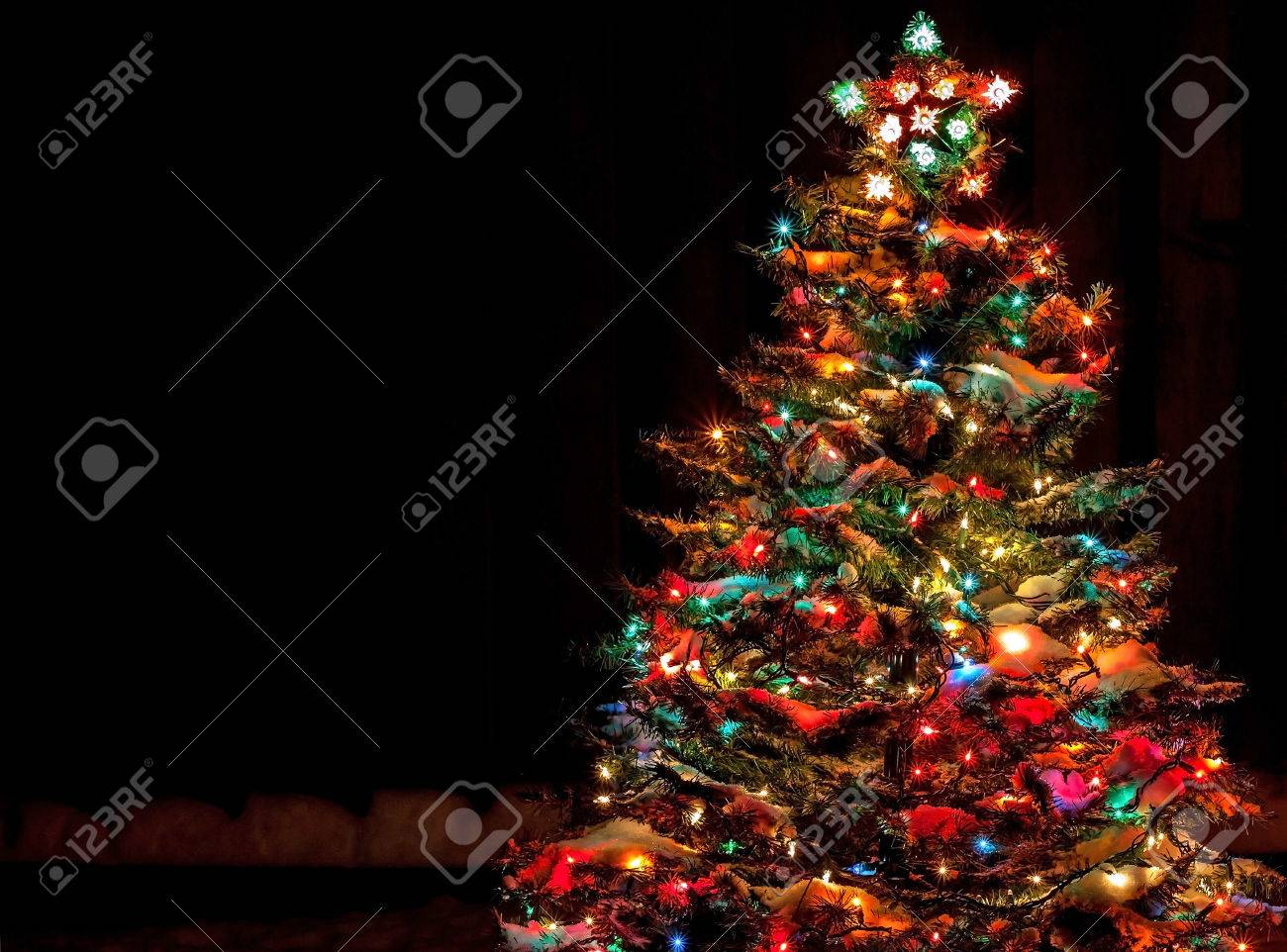 snow covered christmas tree with multi colored lights stock photo 33176818