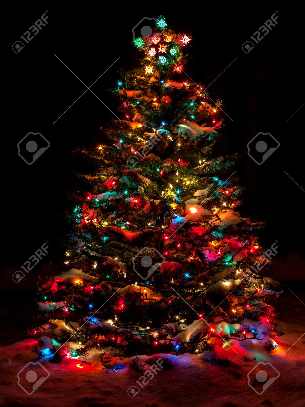 snow covered christmas tree with multi colored lights stock photo 33176820