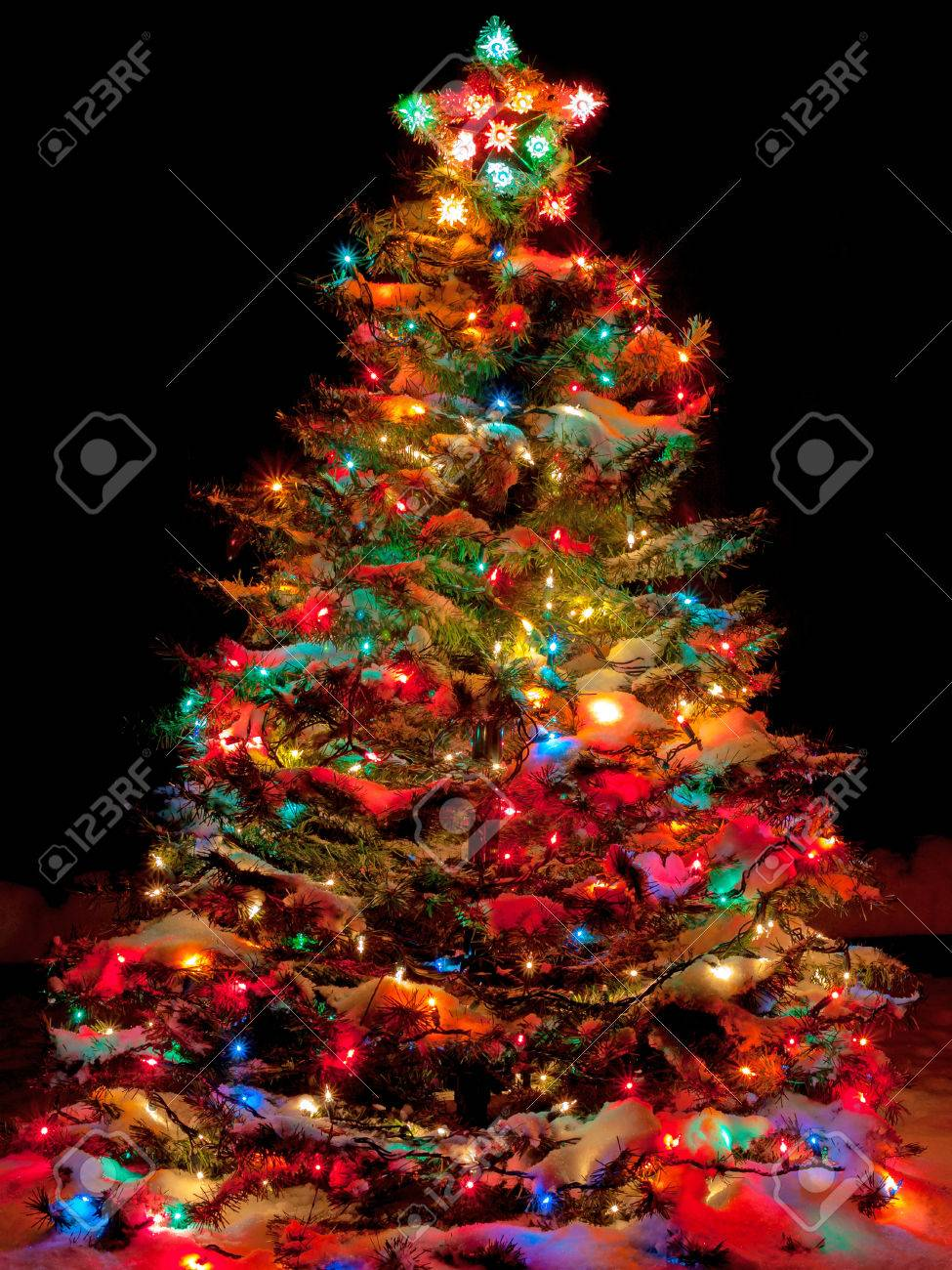 snow covered christmas tree with multi colored lights at night stock photo 33176825