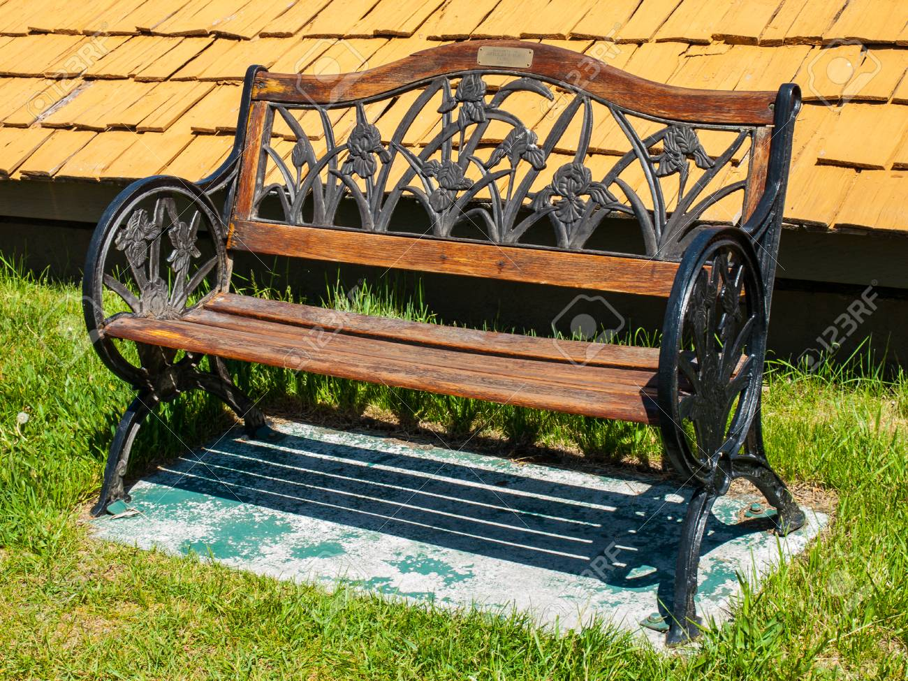 Black Metal And Brown Wood Park Bench On A Sunny Day Stock Photo