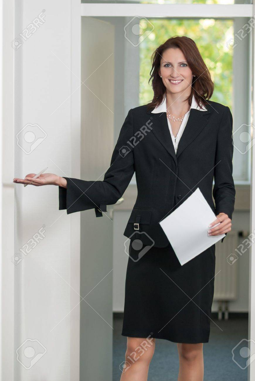 Businesswoman asks to come in into the office Stock Photo - 15599652