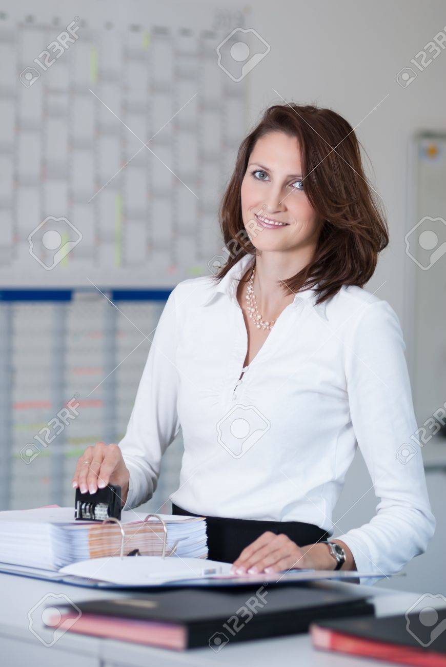 young office clerk stamps documents in the office stock photo stock photo young office clerk stamps documents in the office