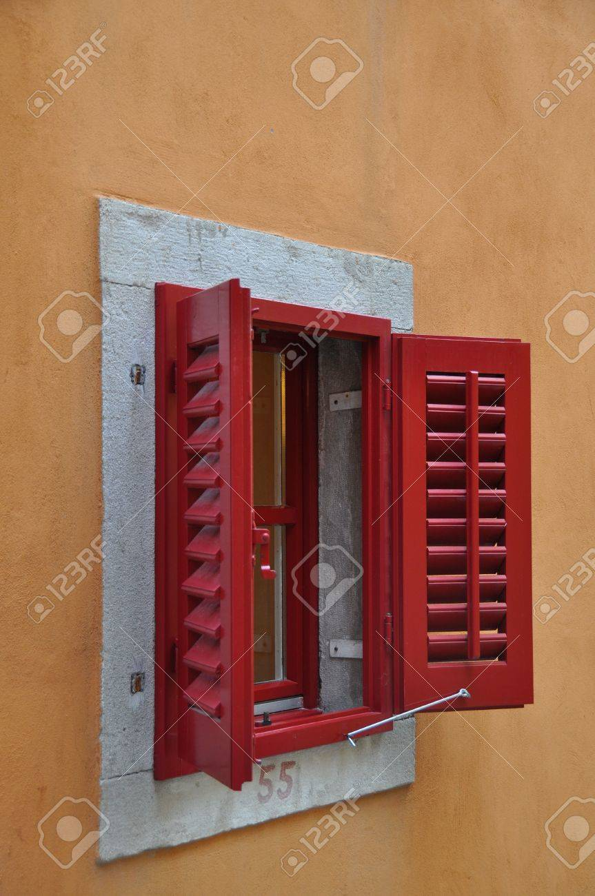 Red Window Shutters Opened On A Bright Frame Above A Terracotta
