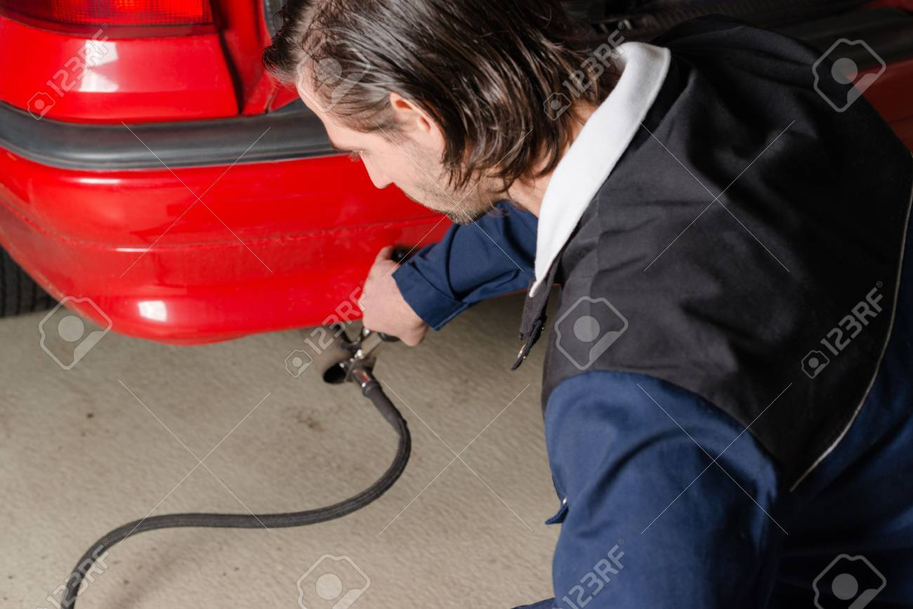 A Mechanic Is Applying A Diagnostic Sensor To The Ehaust Of A