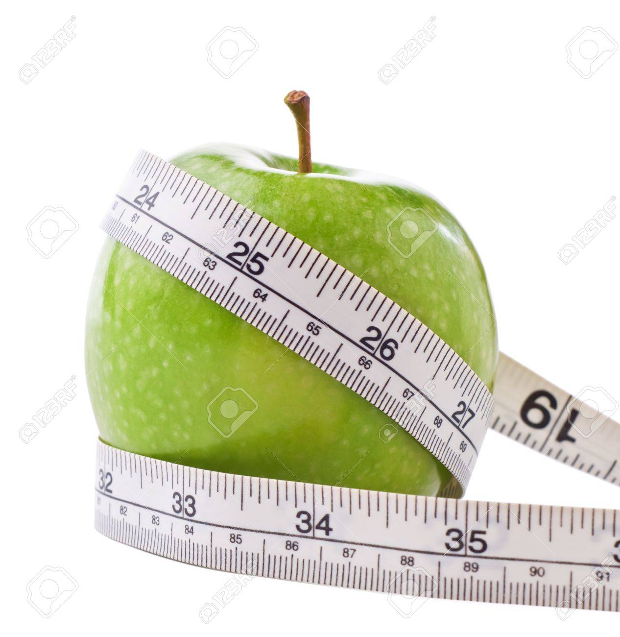 A green shiny Apple, wrapped with a white metric and imperial measuring tape to signify dieting and weight loss.  Isolated on white background with slight shadows retained. Stock Photo - 8898230