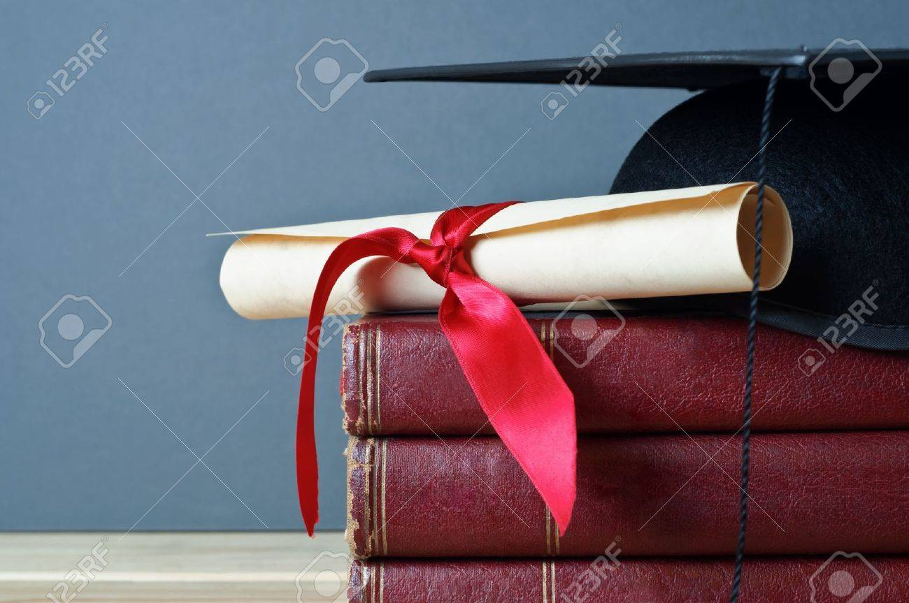 Close up of a mortarboard and graduation scroll on top of a pile of old, worn books, placed on a light wood table with a grey background. Stock Photo - 9177674
