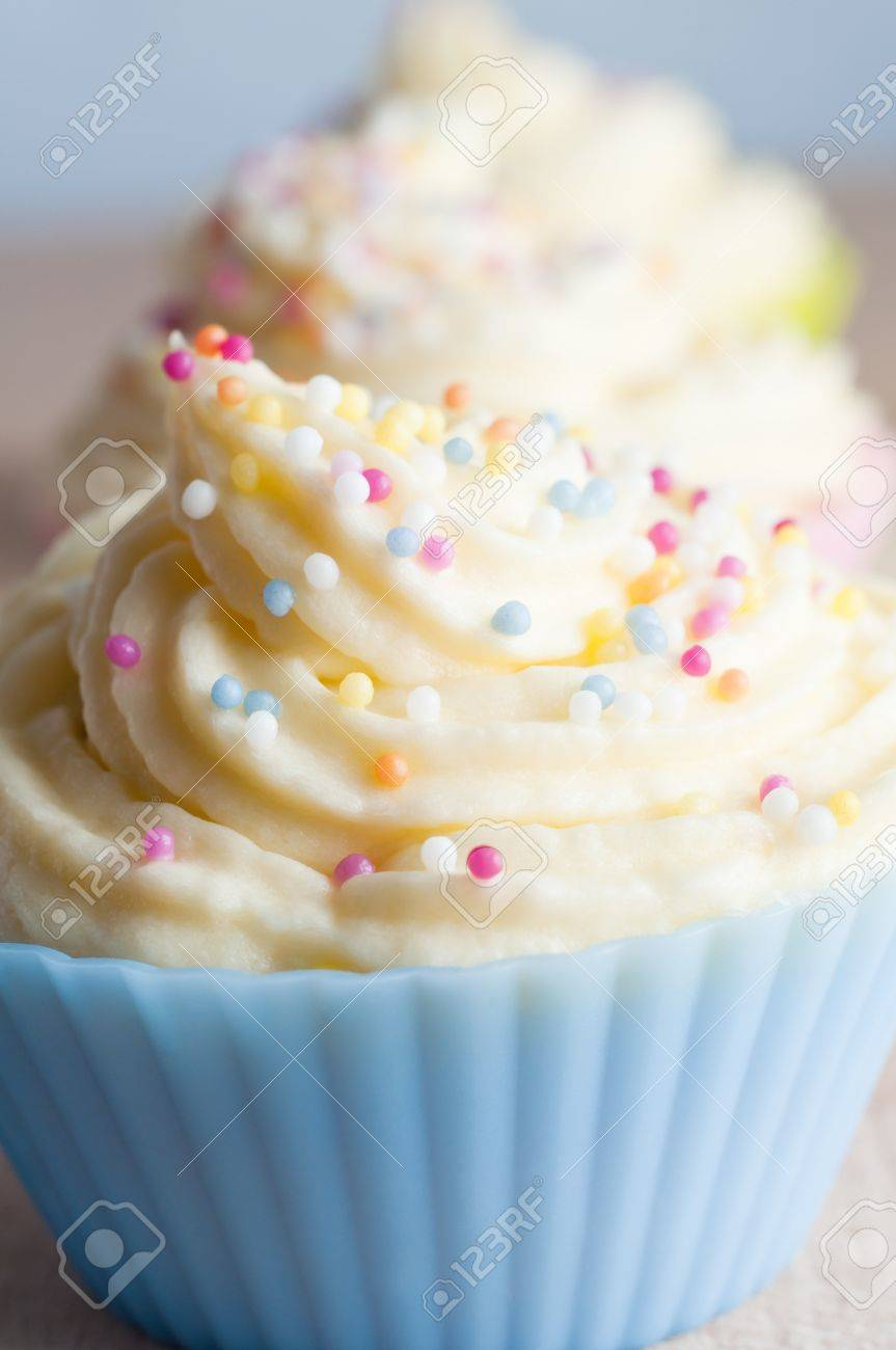 Close up of cup cakes in a row, decorated with swirls of buttercream icing and coloured spherical sprinkles, in pastel coloured cases. Stock Photo - 14003217