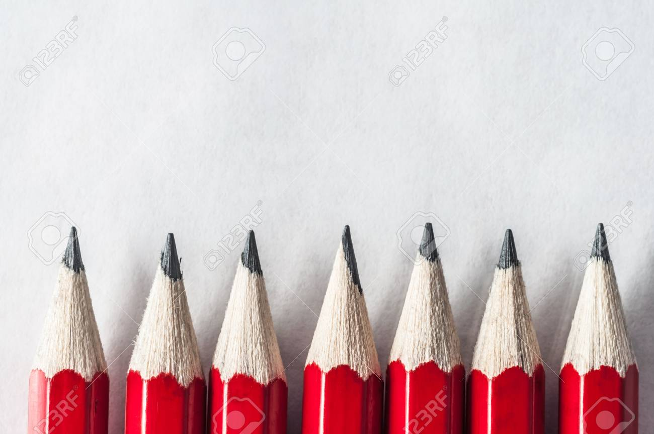 a row of roughly sharpened grubby red pencils on textured art
