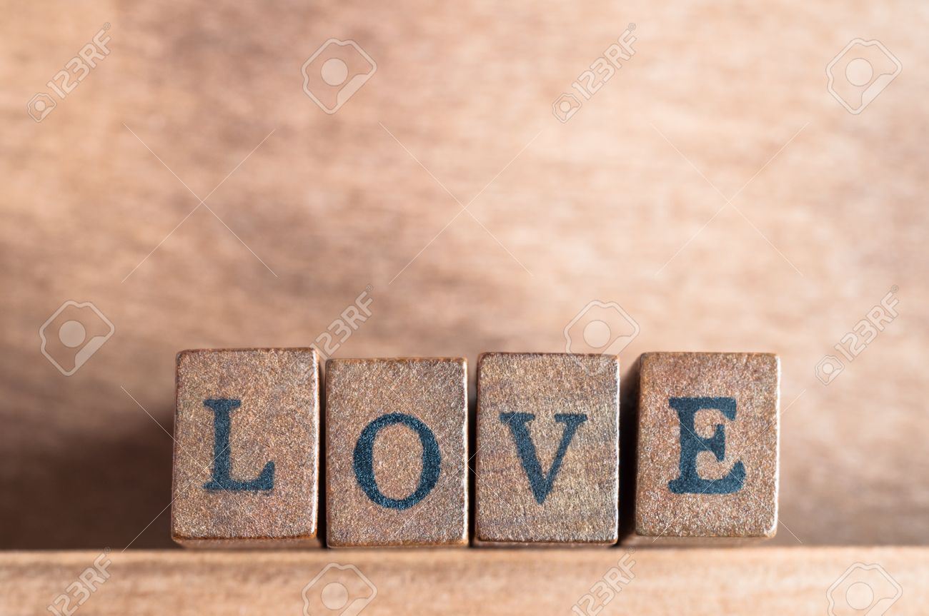 Stock Photo The Word Love Spelled Out On A Row Of Lettered Wooden Blocks With Retro Or Vintage Appearance Facing Forward On A Wooden Shelf With Wood