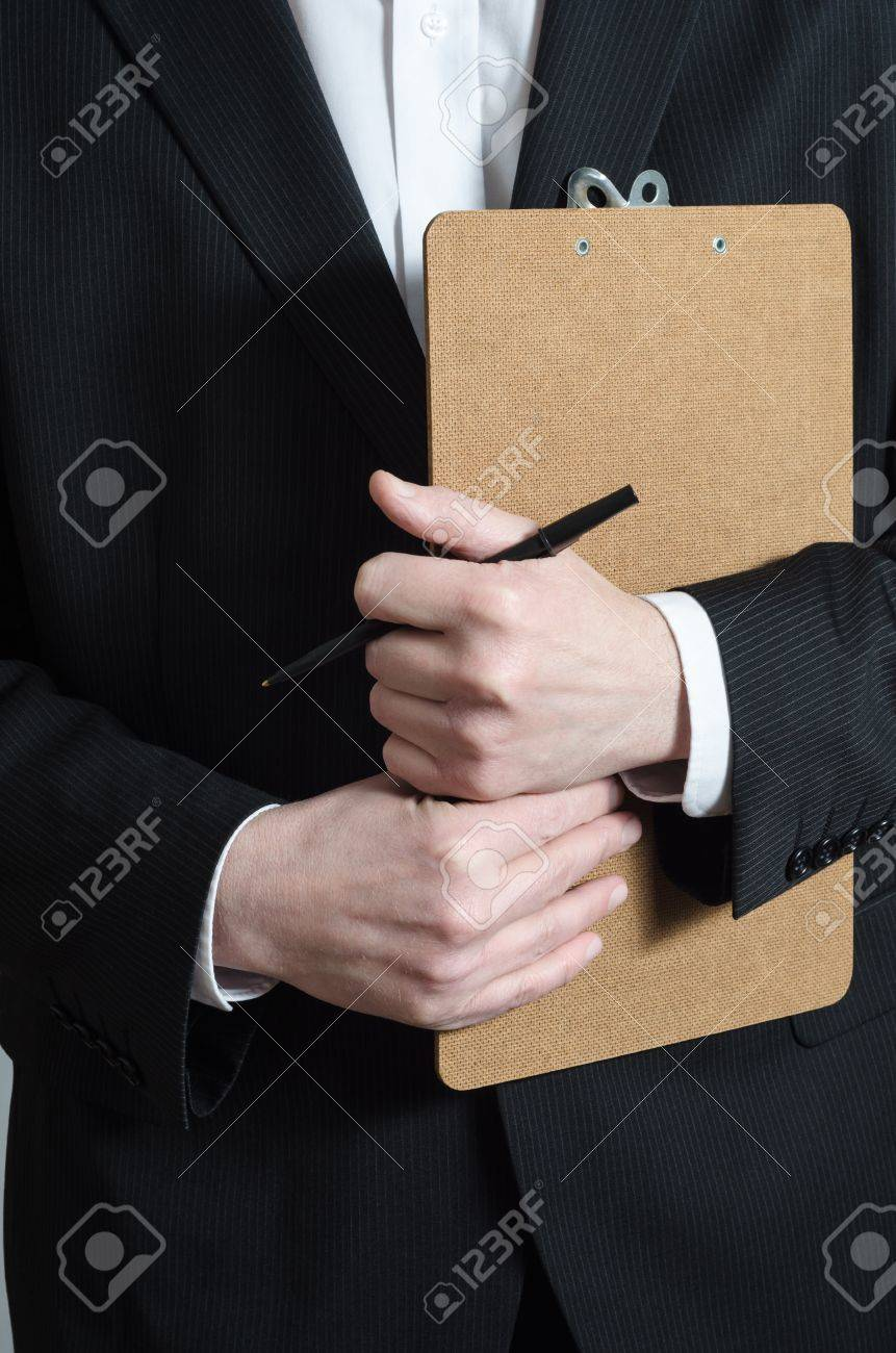 Close up crop shot of a male (torso) in a dark suit and white shirt, holding a clipboard and pen, waiting to collect research data or to confirm a booking or check his list. Stock Photo - 17848418