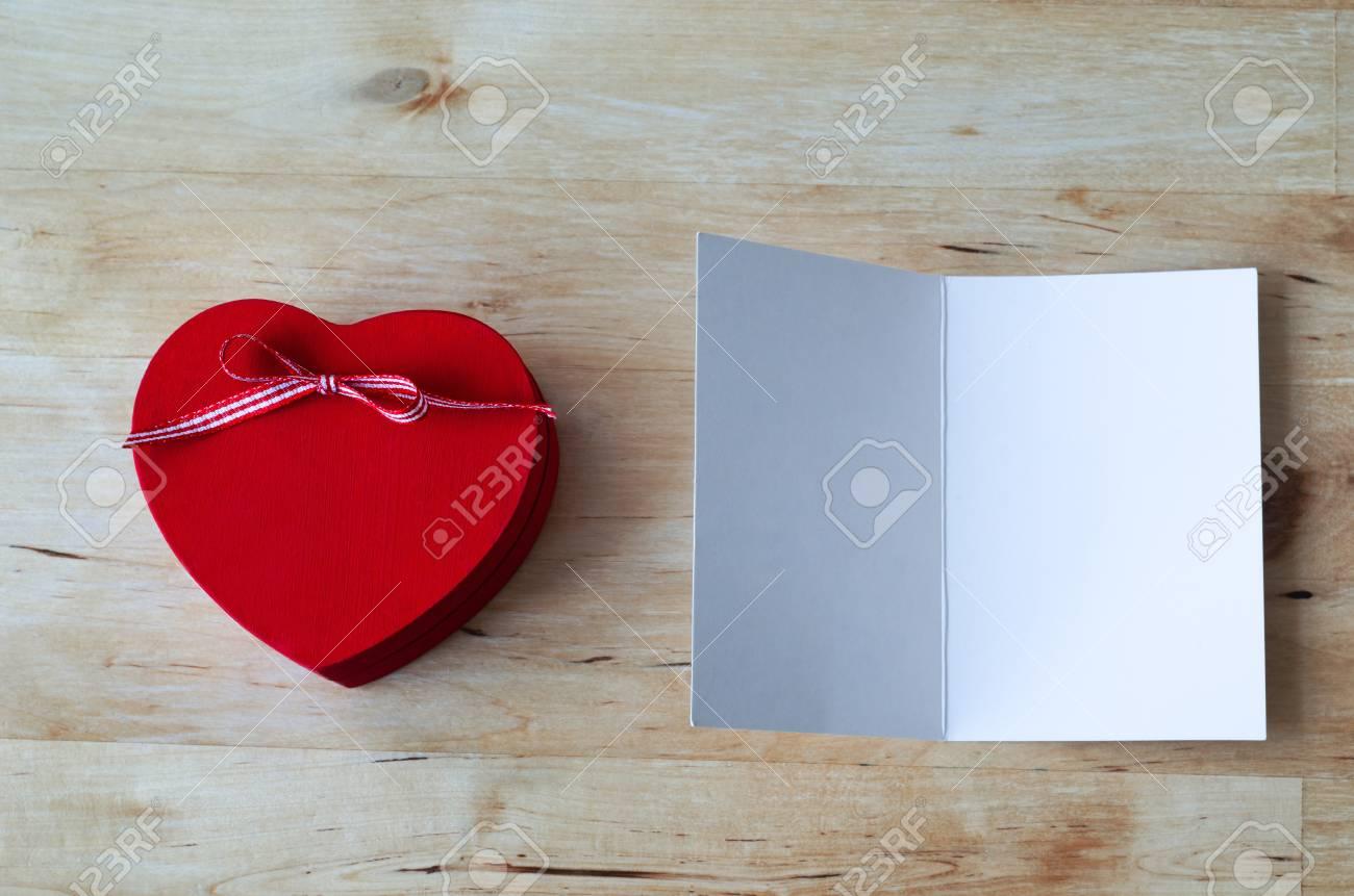 Tiro De Arriba De Una Caja De Madera Pintada De Rojo En Forma De Corazón De Regalo Con Lazo De Cinta Y Una Tarjeta De Felicitación Abierto Dejan En