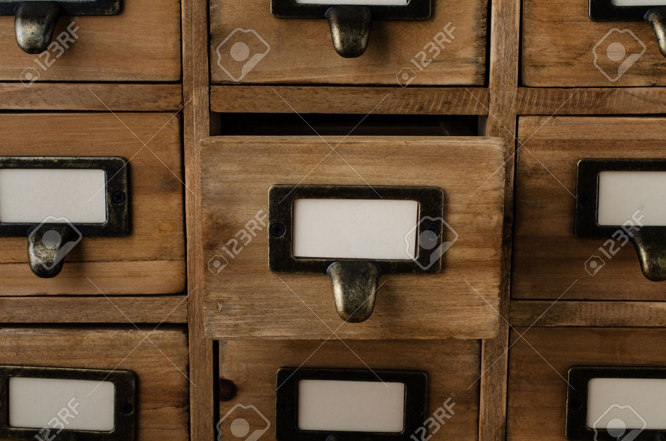 An Old Style Wooden Cabinet Of Library Card Index Drawers With Label  Holders And Blank Labels