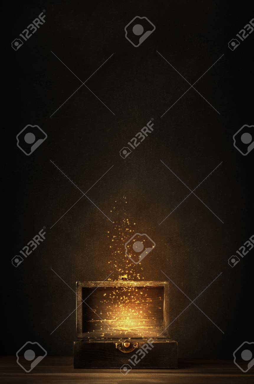 Glowing golden sparkles and stars rising from an old, opened wooden treasure chest. Darkly lit on a planked surface with black chalkboard background. - 88614192