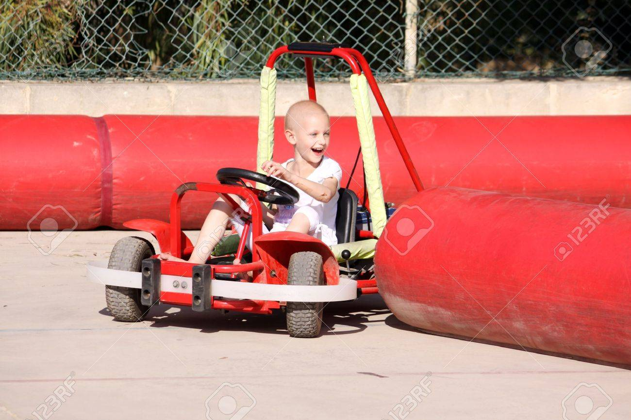 a caucasian child undergoing chemotherapy treatment due to cancer having fun on a go cart at a fun fair Stock Photo - 11425709