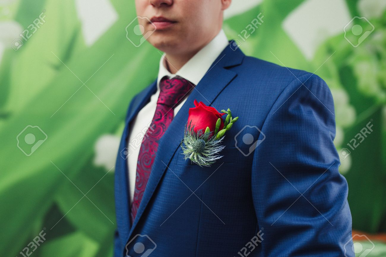 7a8995d43 Groom in a blue suit with a red tie and buttonhole Stock Photo - 49461952