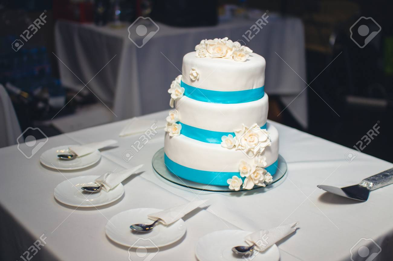 Delicious Wedding Cake With Flowers And Blue Ribbon Stock Photo