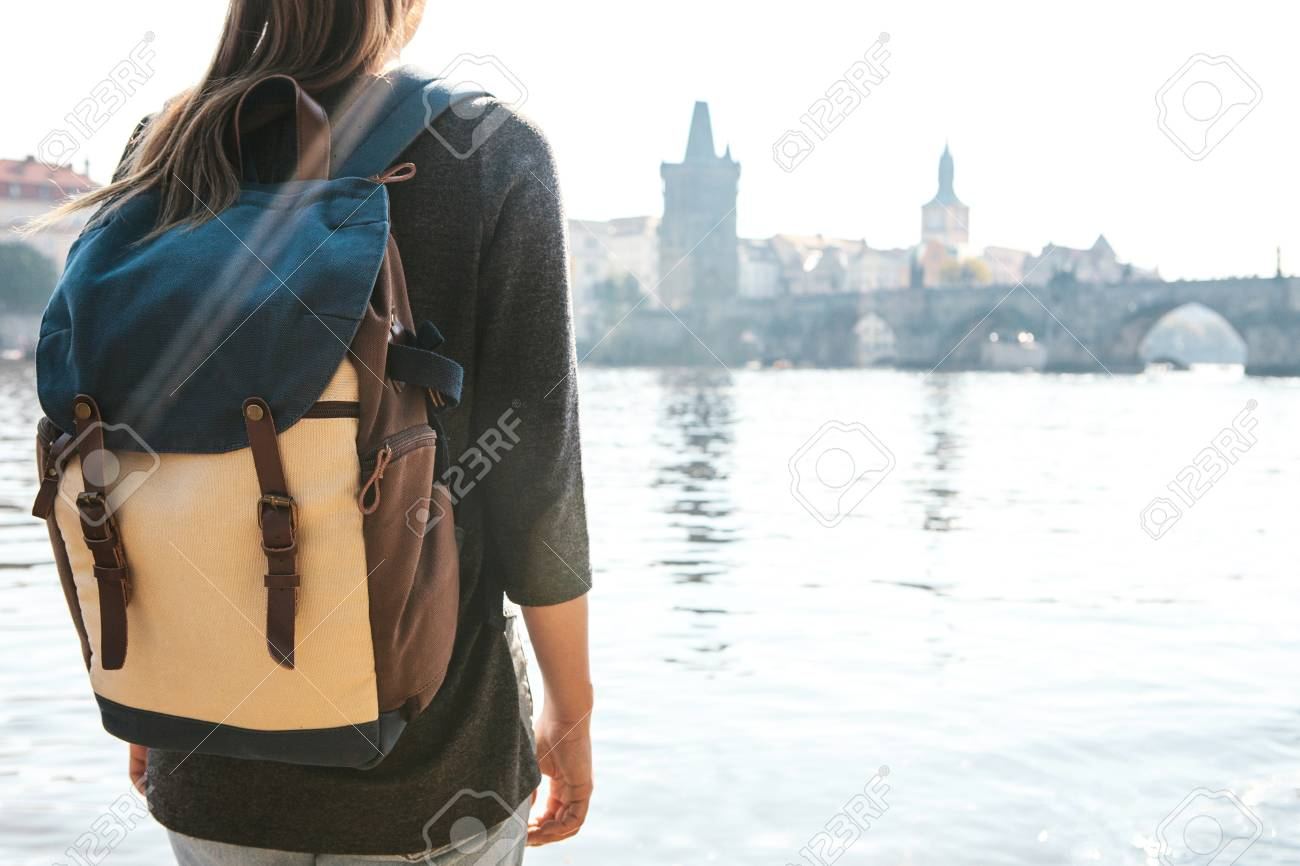 81a12c9eec05 A beautiful young tourist girl with a backpack stands next to the Vltava  river in Prague