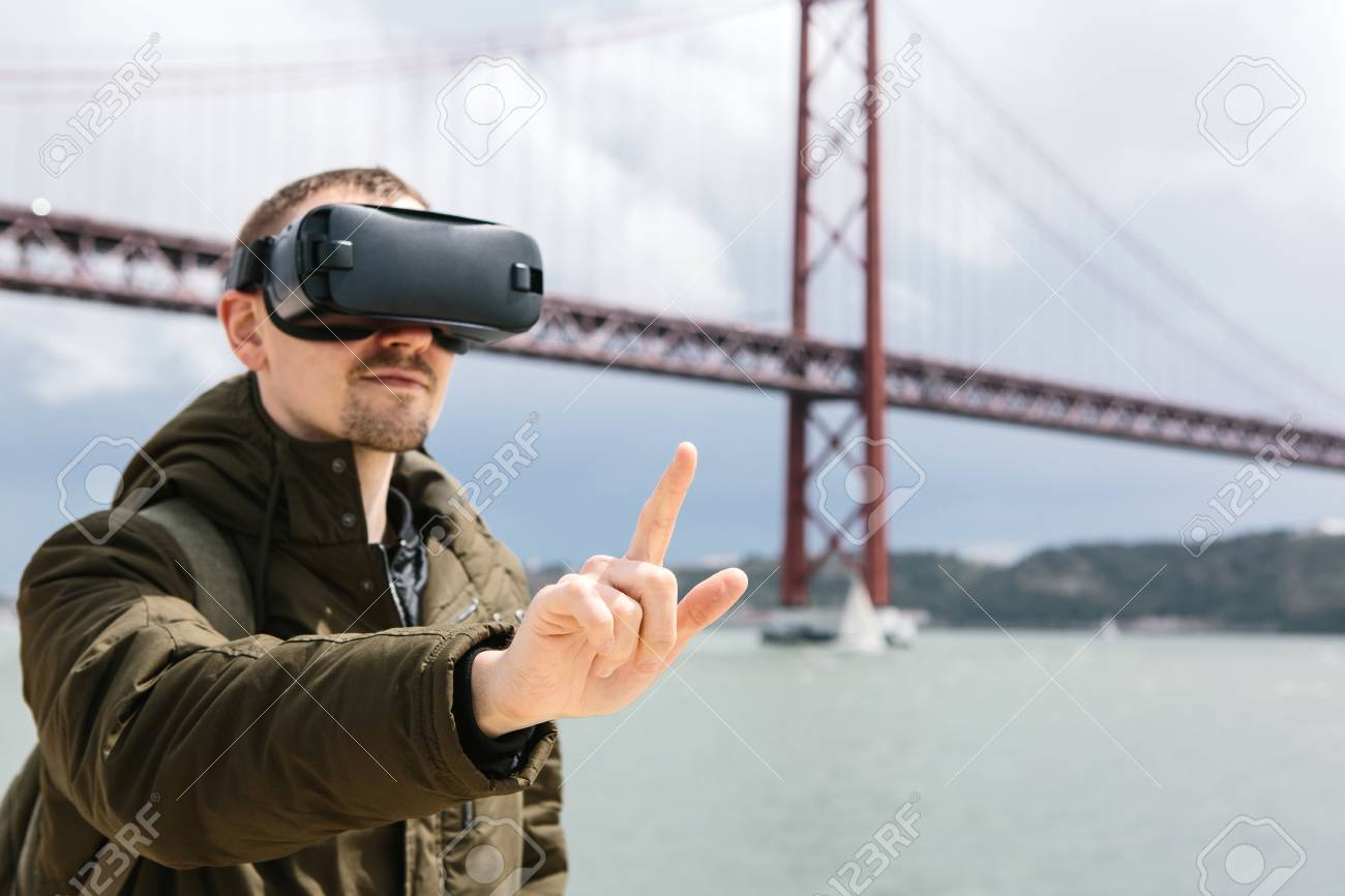A man uses virtual reality glasses. 25th of April bridge in Lisbon in the background. The concept of virtual travel. The concept of modern technologies and their use in everyday life - 101589144
