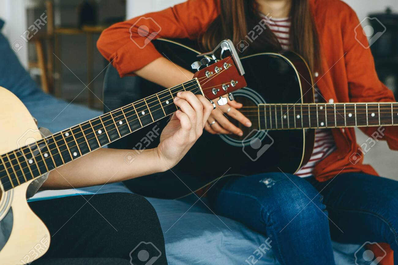 Learning to play the guitar. The teacher explains to the student the basics of playing the guitar. Individual home schooling or extracurricular lessons. - 148267794