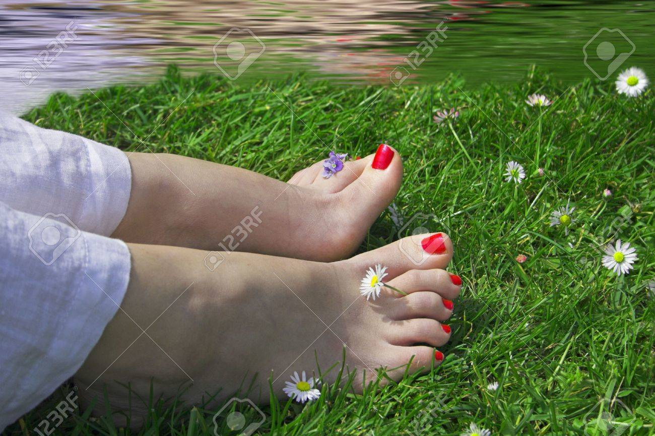 Woman Feet On Grass Near Water With Flowers Around Stock Photo
