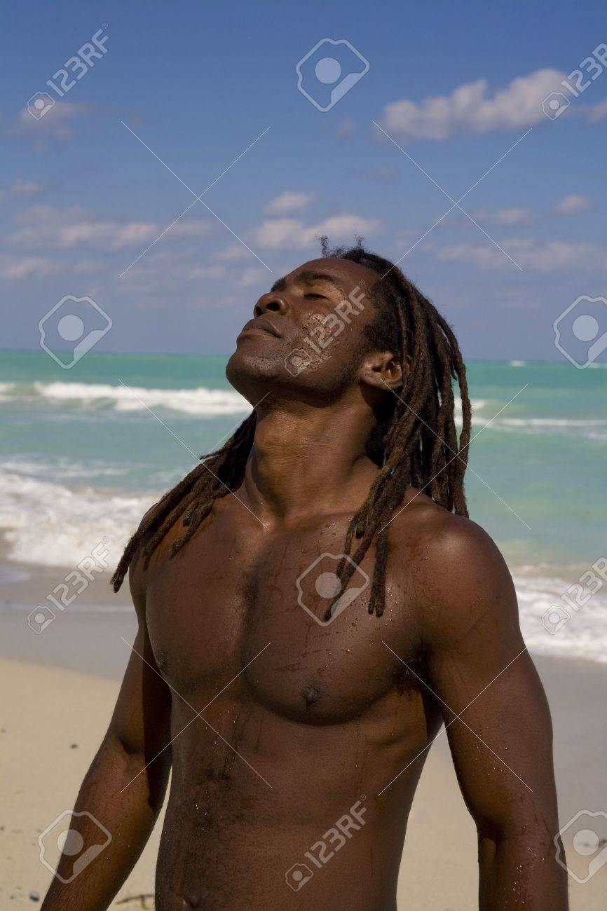 black man tilting his head behind on the beach over blue sea and blue sky Stock Photo - 10375047
