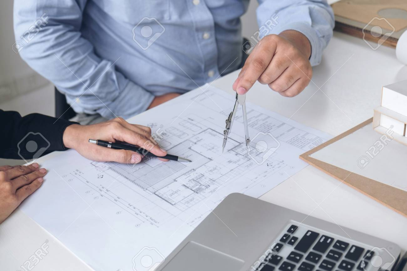 Engineering or creative architect in construction project engineers engineering or creative architect in construction project engineers hands working with compasses on construction blueprint malvernweather Gallery