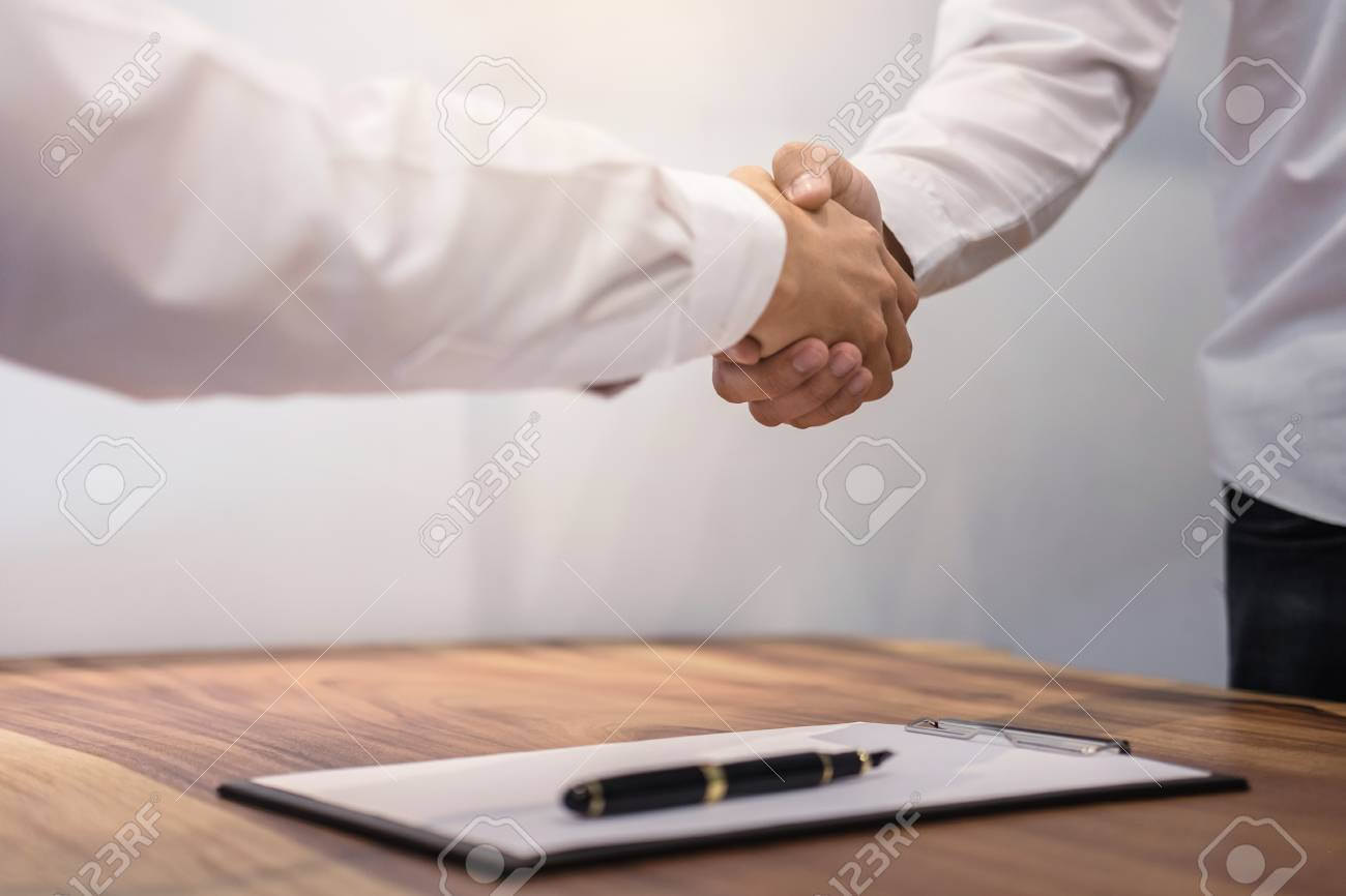 Real estate broker agent and customer shaking hands after signing contract documents for realty purchase, Bank employees congratulate, Concept mortgage loan approval. - 88291772
