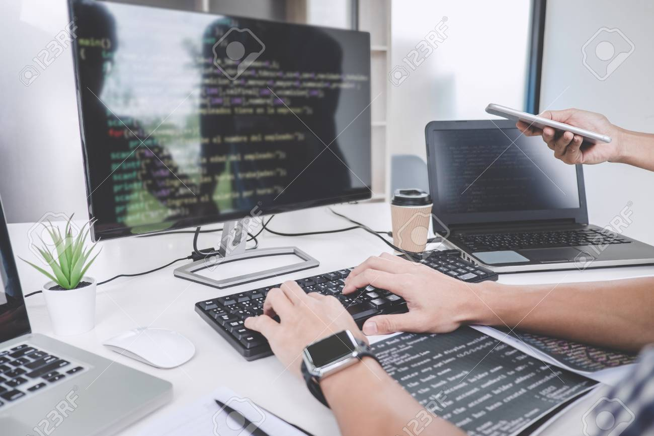 Programmers cooperating at Developing programming and website working in a software develop company office, writing codes and typing data code. - 113602410